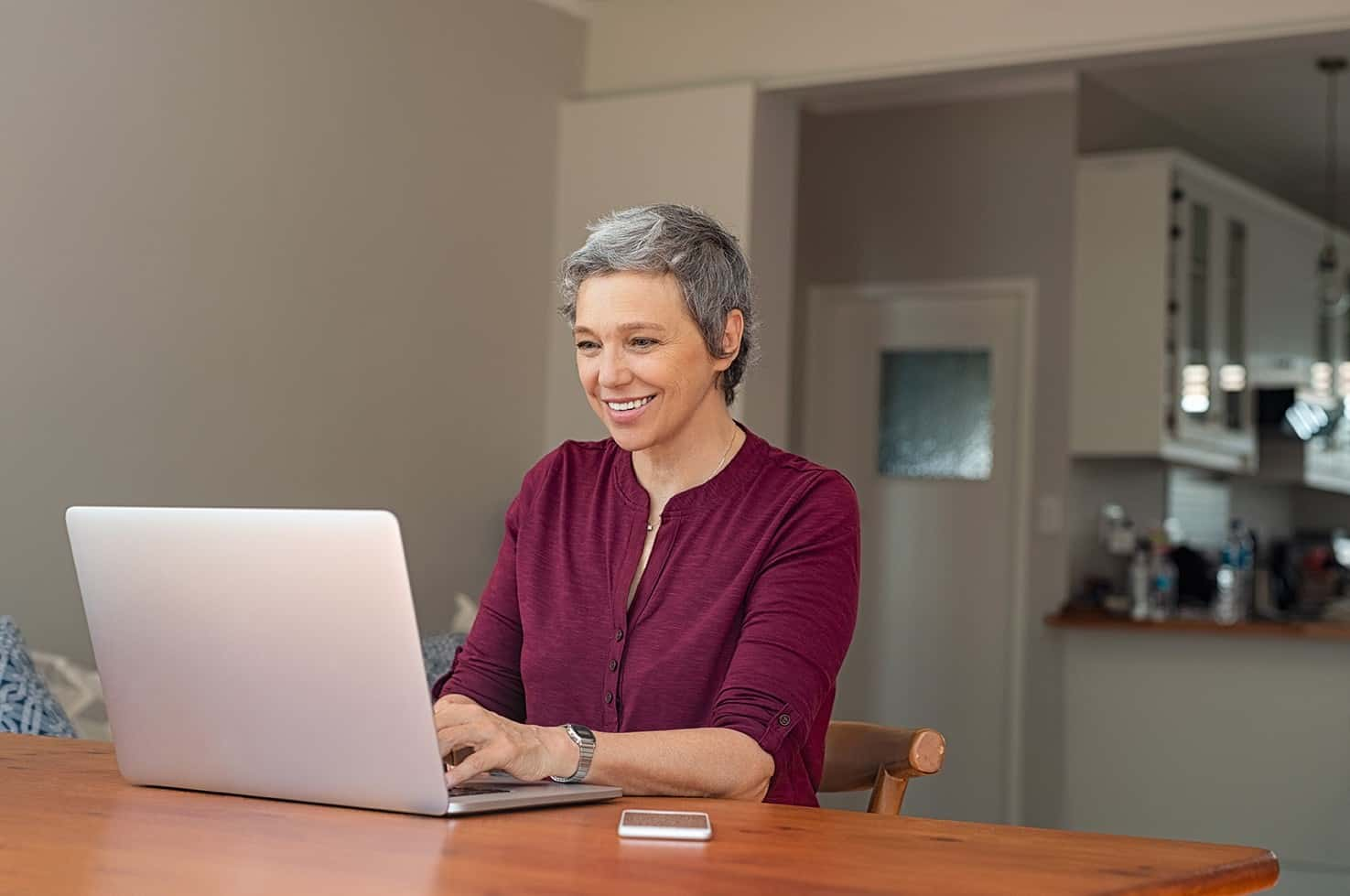 Beautiful senior woman using computer at home