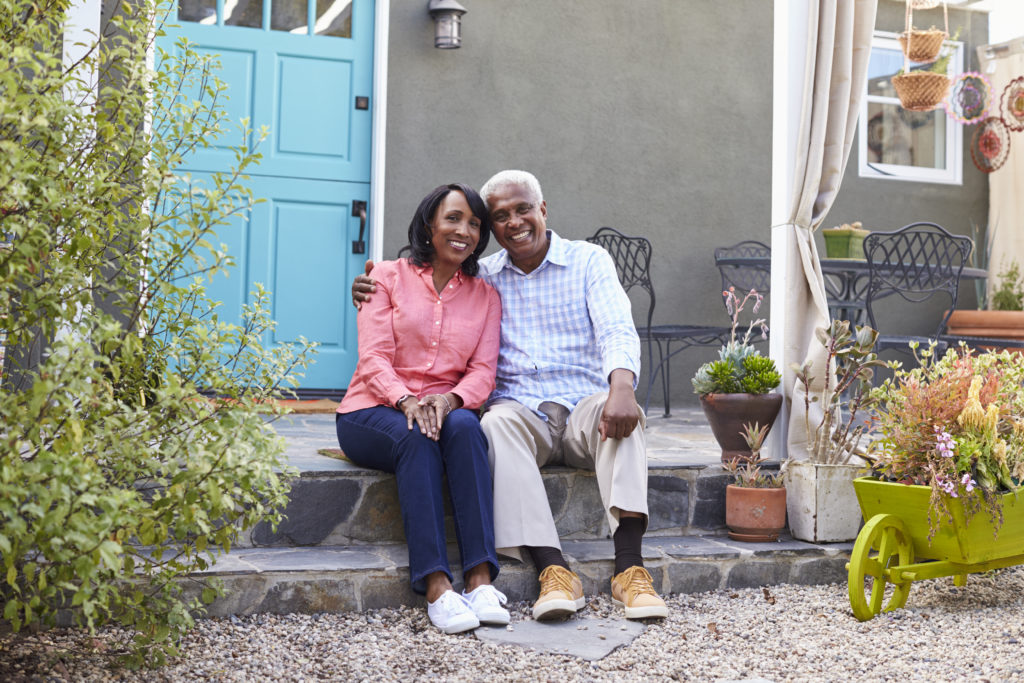 Senior couple sit on steps outside their house